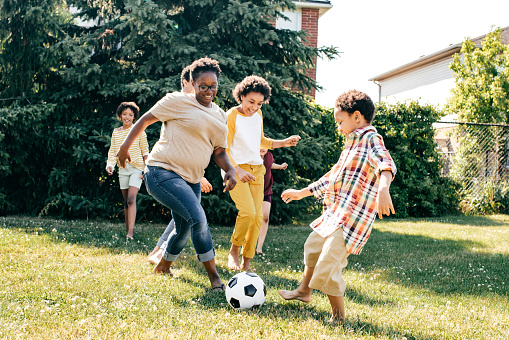 Foster mother playing soccer with children.